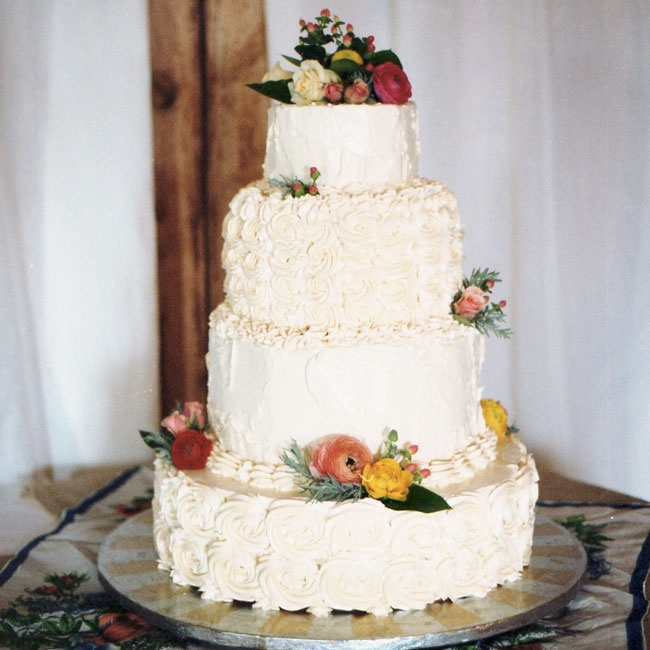 The couple gave friend and caterer John Schopp free range when it came to decorating their rustic four-tier white buttercream cake topped with fresh flowers.