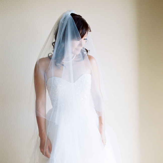 A beautiful Reem Acra gown was chosen by Reimi for the ceremony. The beaded bodice and tulle added a hint of glamour to the romantic gown. Reimi completed her look with a string of pearls and a simple yet elegant mid-length veil.