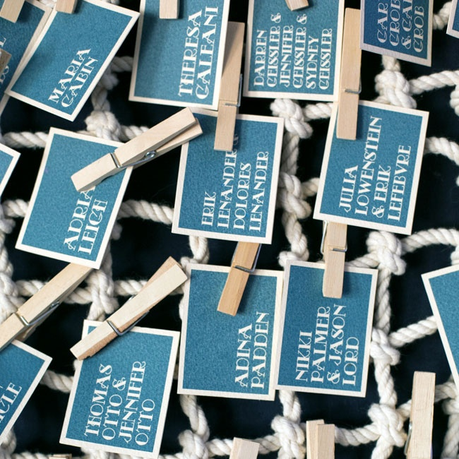 Simple navy escort cards hung from thick nautical rope.