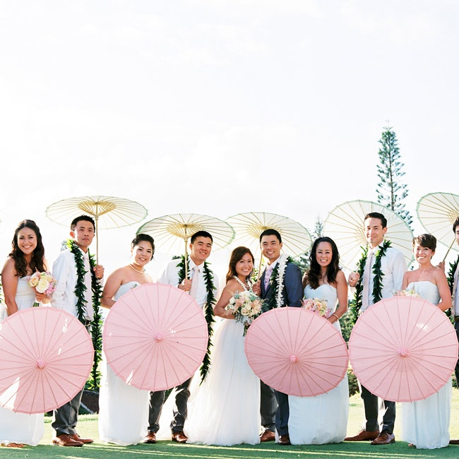 The bridal party posed with pretty pink and white parasols.