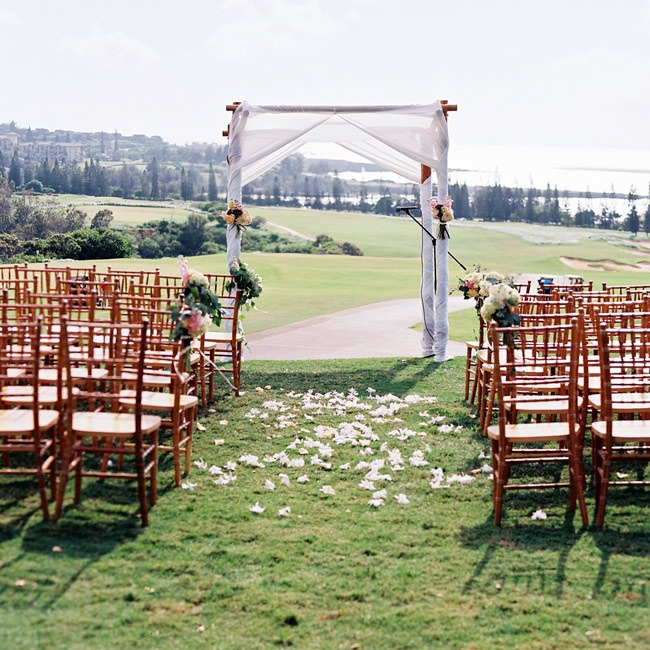 The ceremony took place on the Plantation House's golf course with a fantastic view of the Pacific Ocean. A fabric draped wedding arch, chiavari chairs and an aisle of plumeria flowers created a romantic and intimate atmosphere.