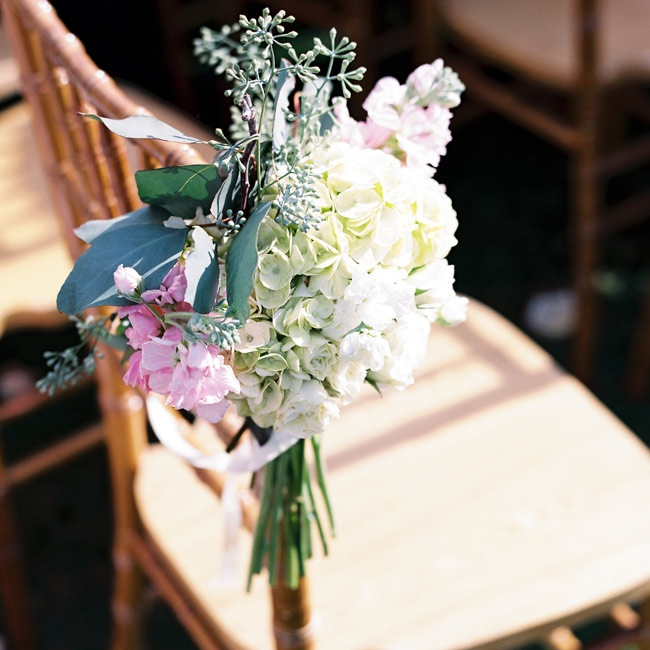 Soft pastel bouquets of hydrangeas and snapdragons lined the aisles.