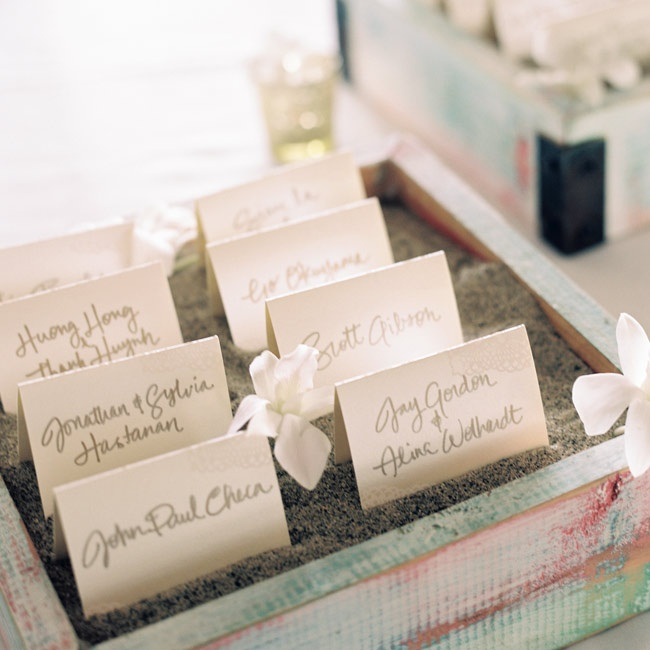 Champagne colored escort cards with gold calligraphy were set in Maui sand and accented with plumeria.