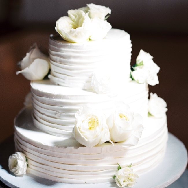 The three-tiered cake was accented by combed buttercream frosting and white cabbage roses.