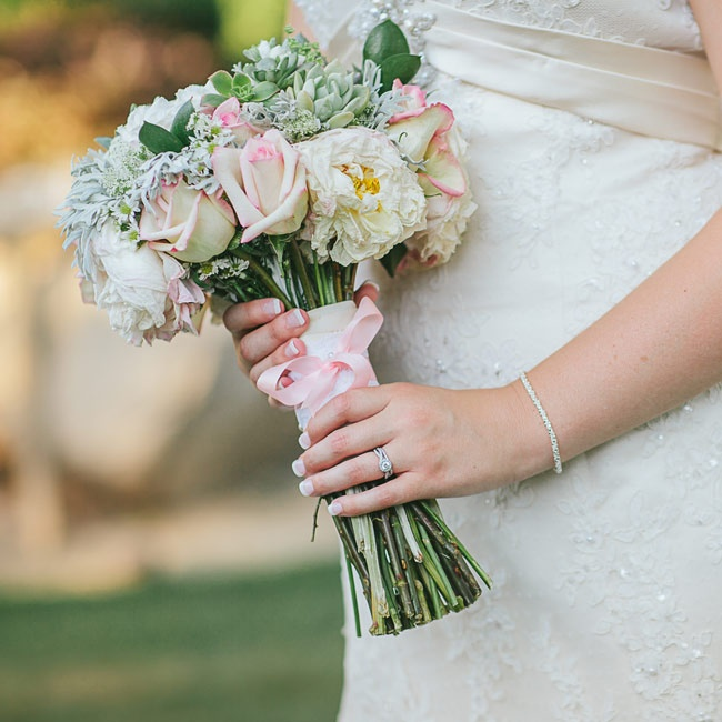 The couple chose a pale pink color palette that introduced a softness to the wedding's rustic ranch details. Pale pink roses and white peonies paired with rustic accents like dusty miller filled Madison's bridal bouquet.