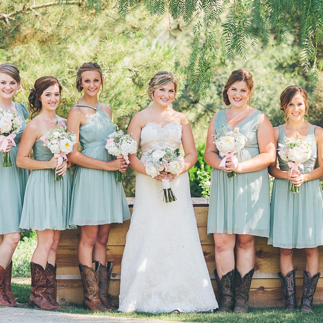 Mismatched dusty shale bridesmaids dresses by J Crew mixed with cowboy boots created a fun, casual look for Madison's bridesmaids.