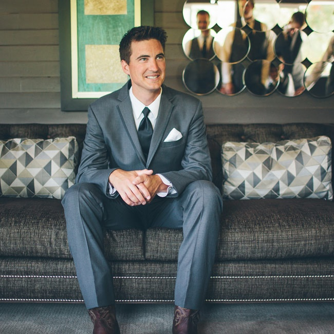 Brent wore a classic grey suit with a black tie and white pocket square. The groom tied in the day's theme to the outfit by sporting a pair of cowboy boots.