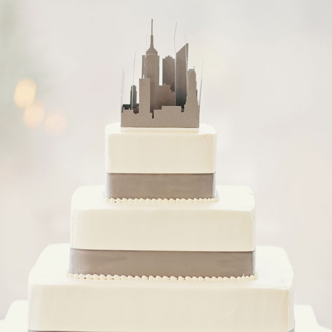 A modern cityscape cutout crowned the modern gray and white cake.