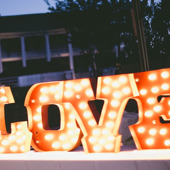"Marquee letter lights spelling out ""LOVE"" highlighted the day's theme and added a modern touch to the reception decor."