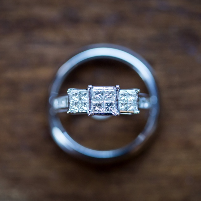 Abby's ring has three prominent square cut diamonds while Greg's ring is a simple platinum band.