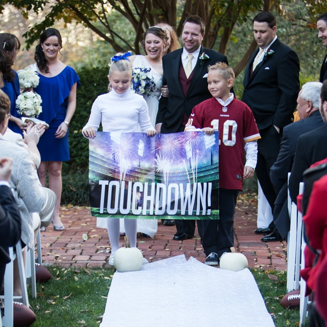 "The newlyweds exited the ceremony behind a wedding sign that read, ""Touchdown!"""