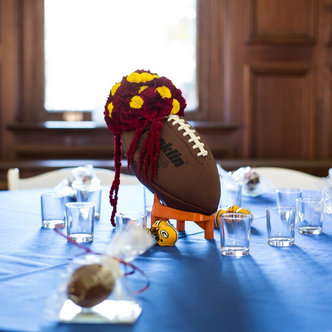 Burgundy and yellow flowers depicted the groom's favorite team (The Washington Redskins) while the blue tablecloth represented the bride's favorite team (The New York Giants). Small plastic helmets illustrated the table name.