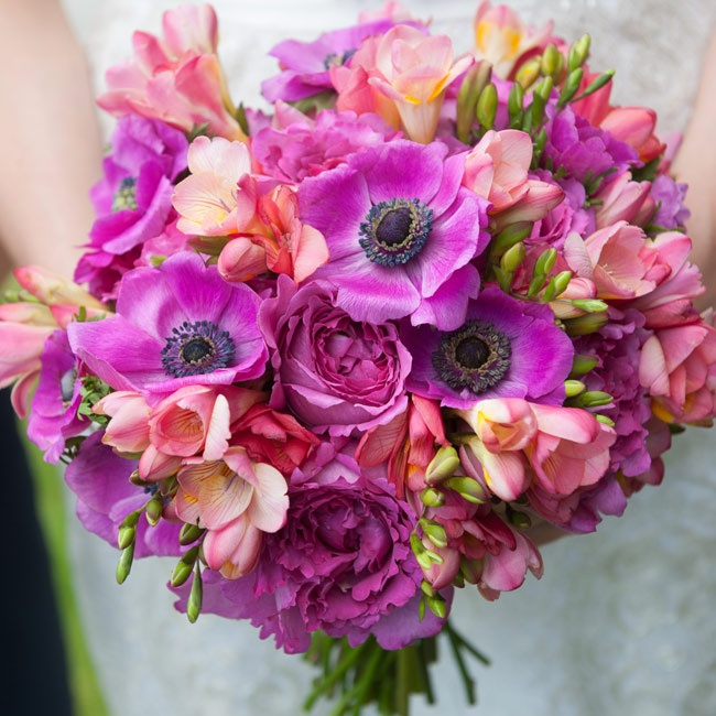 The bride carried an array of tropical flowers including vivid purple anemones.