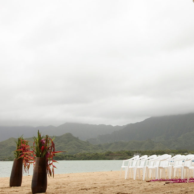 The couple exchanged vows on the beach overlooking the Pacific ocean with tropical floral decorations.