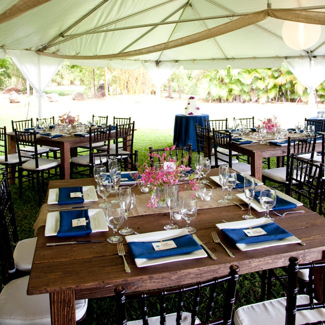 Rustic wooden square tables with black Chiavari chairs, white square plates and blue napkins made up the reception decor.