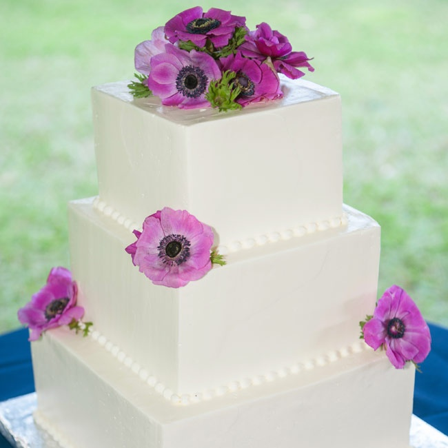 The traditional three-tiered white square cake was topped with fresh purple anemone flowers.