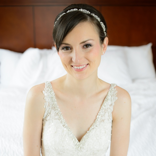 An Erica Koesler headpiece embellished with crystals, pearls and rhinestones adorned Sarah's hair. She completed her look with a classic low chignon and subtle makeup.