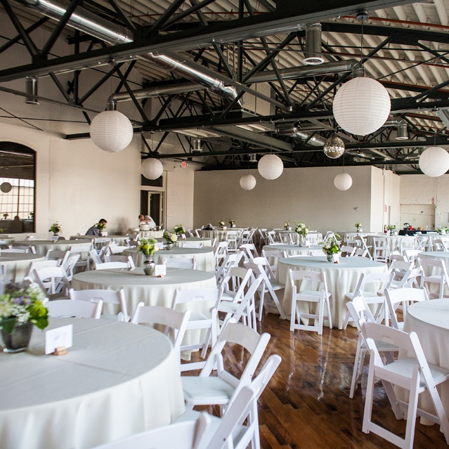 The couple continue their celebrations with family and friends at The Pointe, a historic leather lace and cotton sash factory in Louisville. The space was the perfect mix of modern and historic, with exposed brick and steel beams. White linens and feminine centerpieces softened the space and added a modern touch.