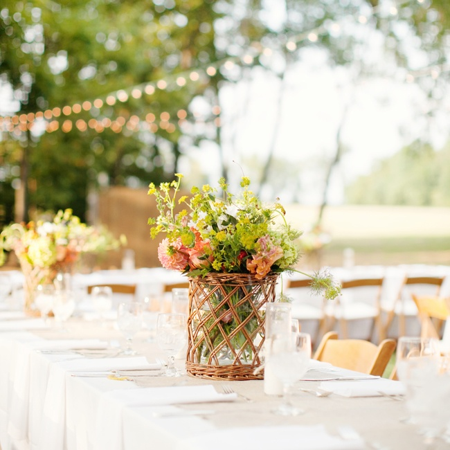 Centerpiece vases were lined with wicker for a rustic touch to the reception decor.