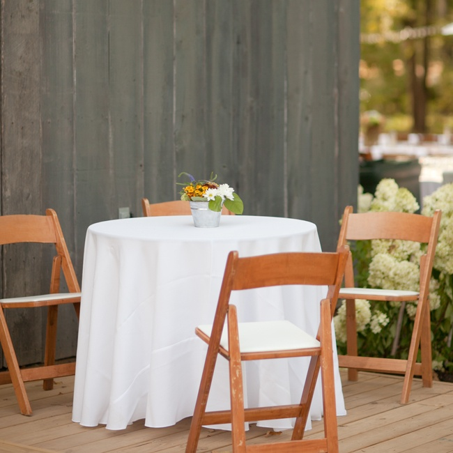 At the reception, guests could take a break from dancing at small round tables decorated with white linen tablecloths and wooden folding chairs.