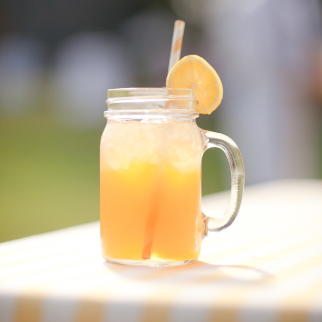 During cocktail hour, guests stayed refreshed with themed yellow cocktails served in Mason jars with handles and yellow striped straws.