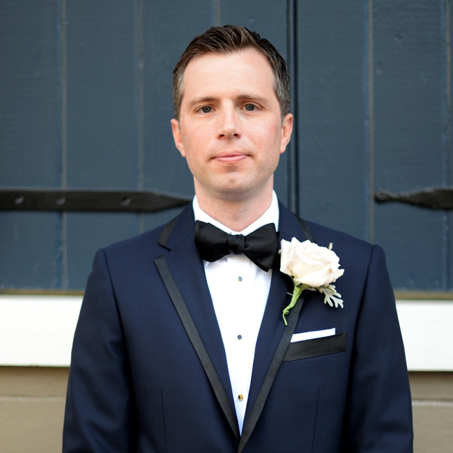 Joel wore a navy tuxedo trimmed in black with a black bowtie and a large, white rose boutonniere accented with dusty miller.