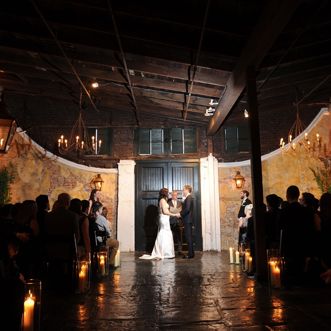 Amanda and Joel's ceremony decor was intimate and darkly lit. Pillar candles and chandeliers illuminated the dark space so that all eyes were on the couple.