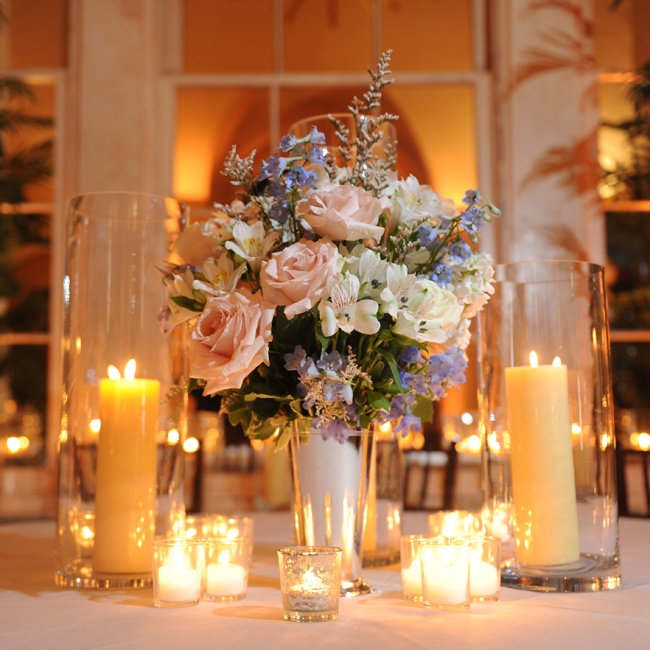 The couple used typical floral centerpieces during the reception, but accented the arrangements by surrounding them with various sizes of candles for an intimate feel.