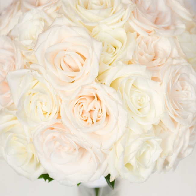 The bride carried a romantic bouquet filled with ivory and blush colored roses down the aisle.