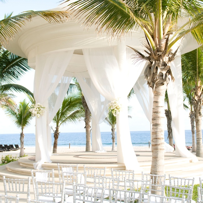 Stephanie and Hector exchanged vows under an elegant gazebo just steps away from beautiful white sands and rolling blue waves. Sheer white linens and floral arrangements added an airy feel to the tropical setting.
