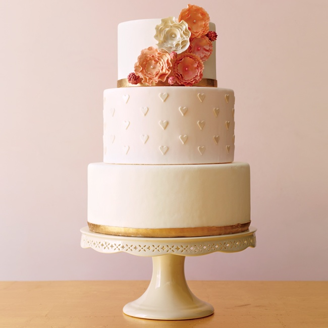 A classic round cake is the perfect backdrop for pattern and embellishments. Here, the iconic heart is repeated in a Swiss dot pattern, giving it a fresh look without overpower the cake's design. Pops of metallic, like gold bands, and eye-catching, pastel sugar flowers (finished with pearl centers) add glitz and texture.