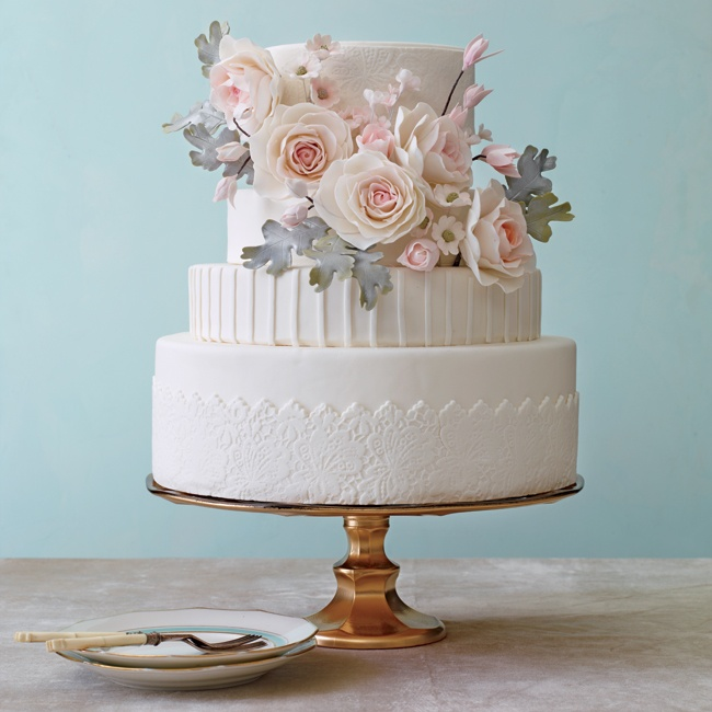 White cakes are the ultimate in understated elegance (not to mention timeless). Better still, they pair perfectly with whatever wedding colors you choose. This classic style gets an update with playful stripes and modern lace accents. Cascading sugar flowers add a 3-D texture and a touch of whimsy.
