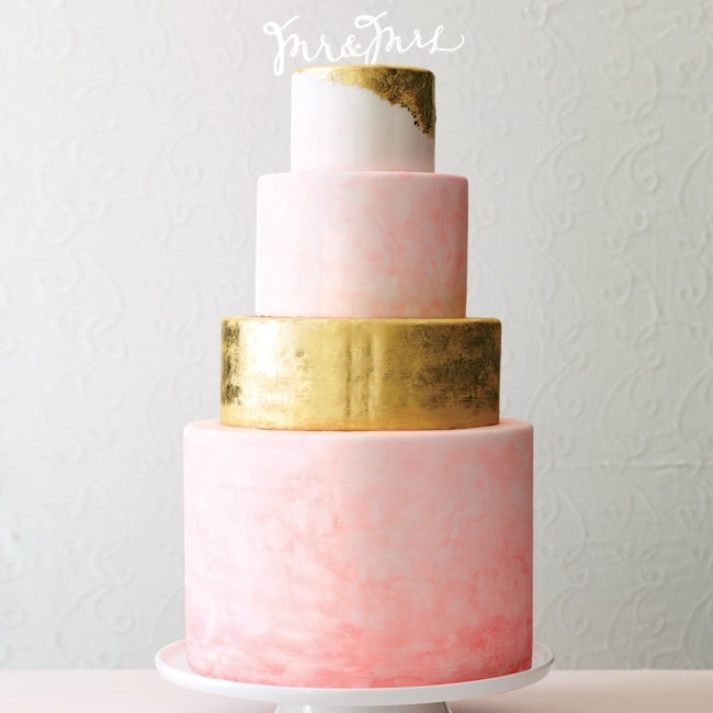"""Gold foil isn't just for stationery. Metallics are popping up in everything from paper and shoes to layers of cake. Hand-painted watercolor tiers add a splash of pink, while keeping the gold from becoming garish. An acrylic scripted """"Mr. & Mrs."""" by Little Cat Design Co. is a contemporary take on the classic bride and groom cake topper."""