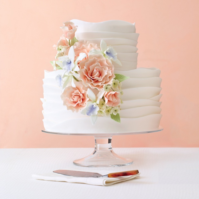 This white cake is anything but boring! Layers of hand-rolled fondant create a rippled wave look--proof that a simple design can make a big impact. A classic cascade of sugar flowers in pastel colors adds dimension and a touch of tradition.