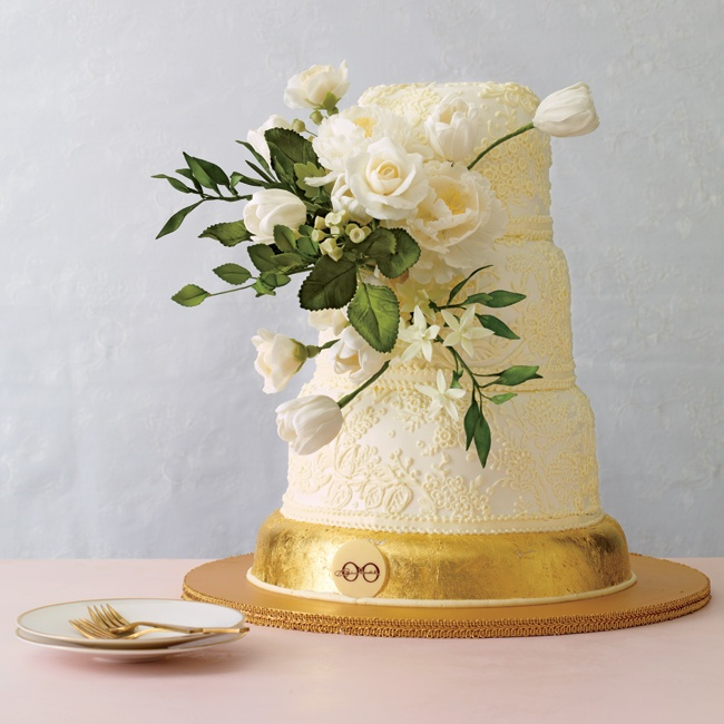 Sylvia Weinstock proves buttercream isn't just for rustic weddings. A delicately piped vintage lace pattern adds depth and deliciousness to each layer. Roses, tulips, peonies, berries and Mokara orchids complement crisp green leaves for a fresh take on sugar flowers. The piece de resistance? A bottom layer covered in edible 24-karat gold leaf.