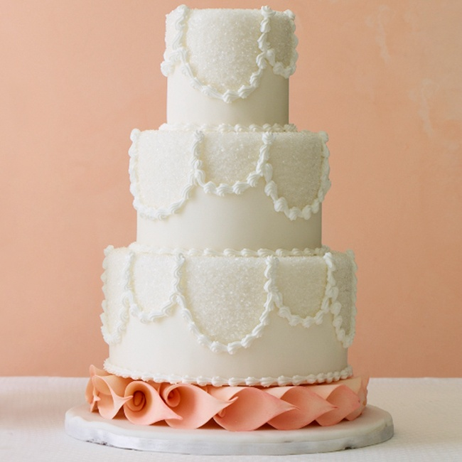 This cake takes traditional to the next level with sprinkled sugar detailing and scalloped white frosting designs on each tier. Add a pop of color at the bottom with soft, pink calla lily sugar flowers.