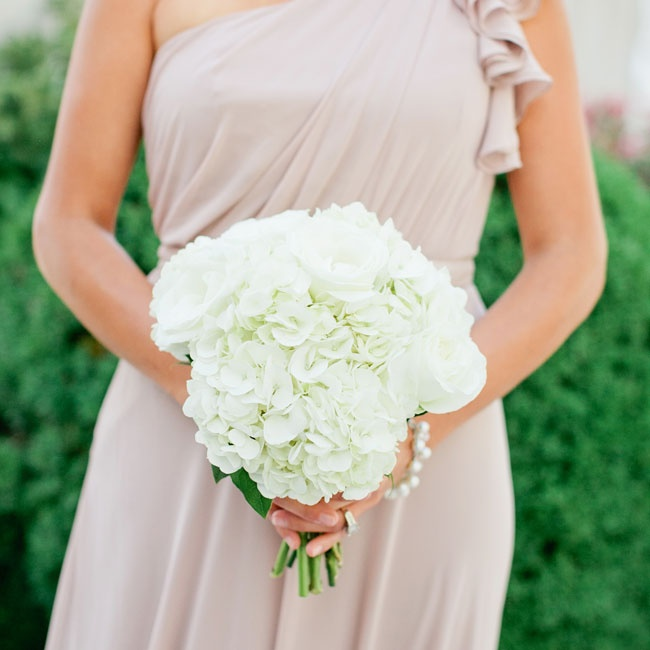 Ronda's bridesmaids carried simple bouquets of white hydrangeas that looked elegant paired with their blush one-shoulder chiffon dresses.