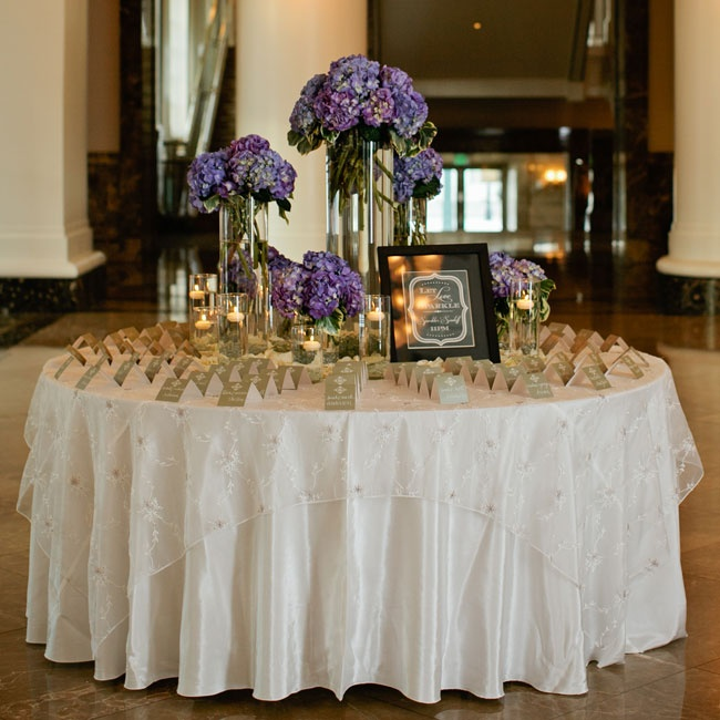 Sage calligraphed escort cards were displayed with bold purple hydrangeas and the soft glow of floating candles.
