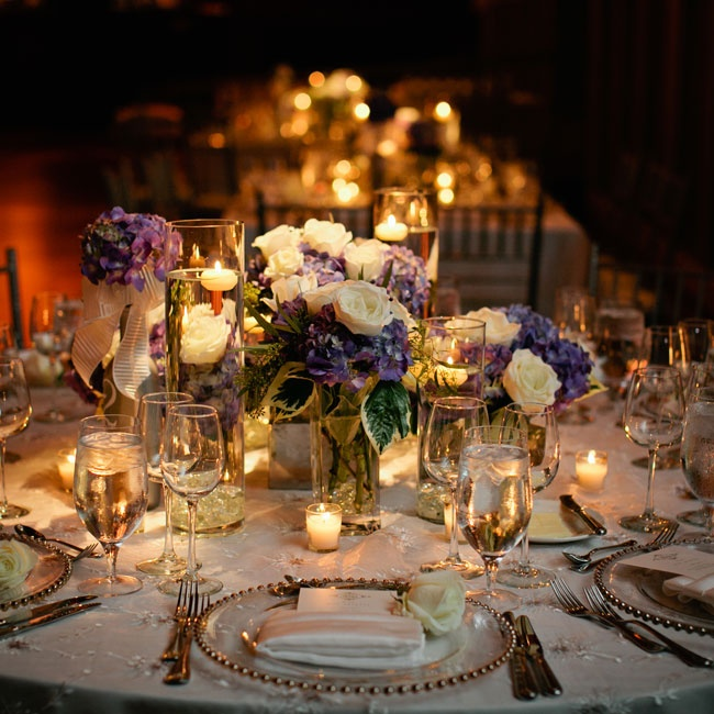 Elegant arrangements of deep purple hydrangeas and white roses combined with the warm glow of candlelight to create an intimate, romantic atmosphere.