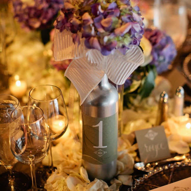 Tables were scattered with white rose petals and silver-painted wine bottles filled with purple hydrangeas displayed the table numbers.
