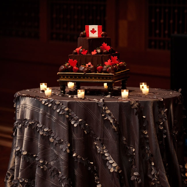 The chocolate buttercream groom's cake was adorned with dozens of chocolate-covered strawberries and red fondant maple lives. A miniature Canadian flag made from fondant topped the delectable creation.
