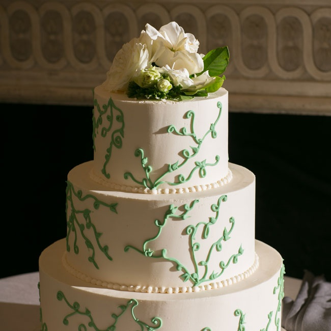 A green vine pattern and a crown of fresh flowers decorated the three tier American buttercream cake.
