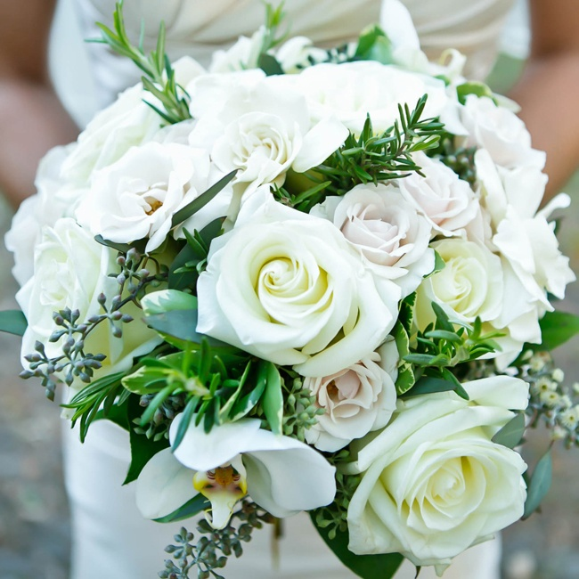 The bridal bouquet was full of white roses and textured with white orchids.