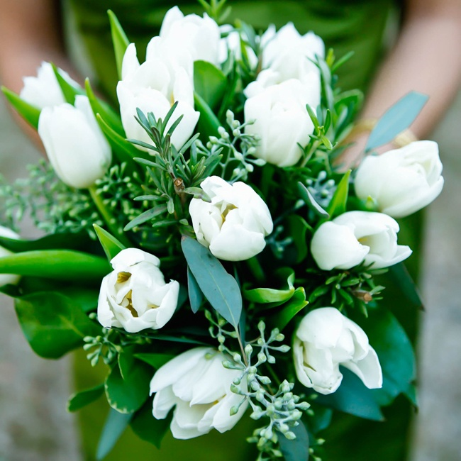 Bridesmaids carried bouquets of white tulips down the aisle during the ceremony.
