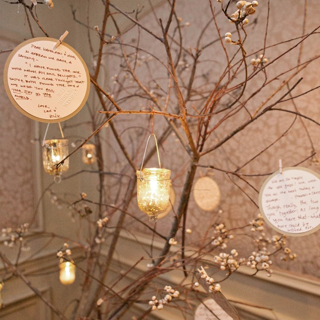 Guests left sentimental notes to the couple attached to this tree decorated with candles.