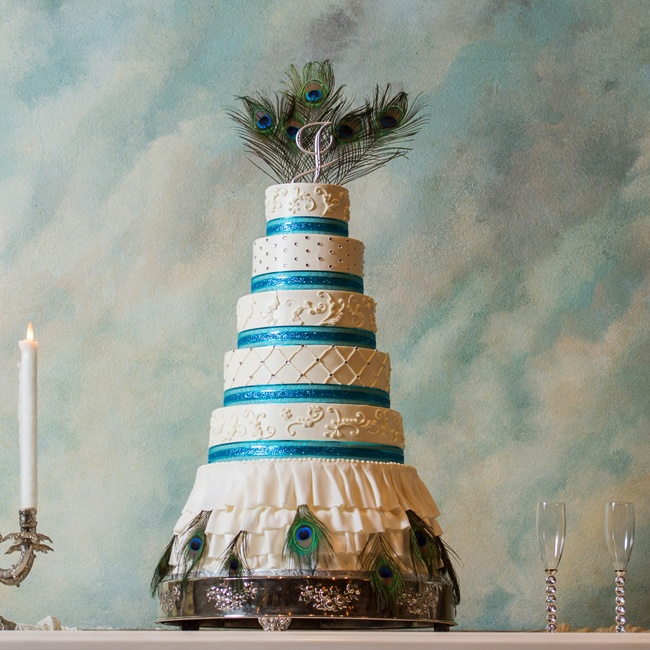 The large white, round, tiered cake was wrapped in jewel-toned teal ribbon and topped with peacock feathers for a dramatic, glam effect.