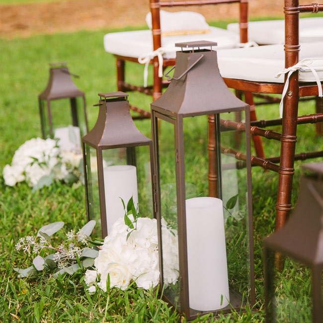 Rustic lanterns with pillar candles lined the aisles and gave off a warm, inviting glow. Bouquets of hydrangeas and eucalyptus leaves added a romantic flair to the ceremony decor.