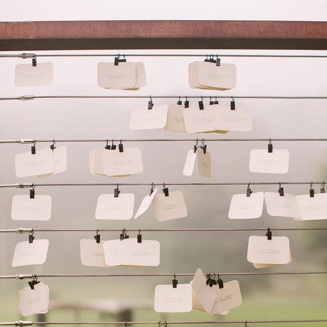 Escort cards hung from a rustic wooden and wire frame for a rustic, vintage flair.