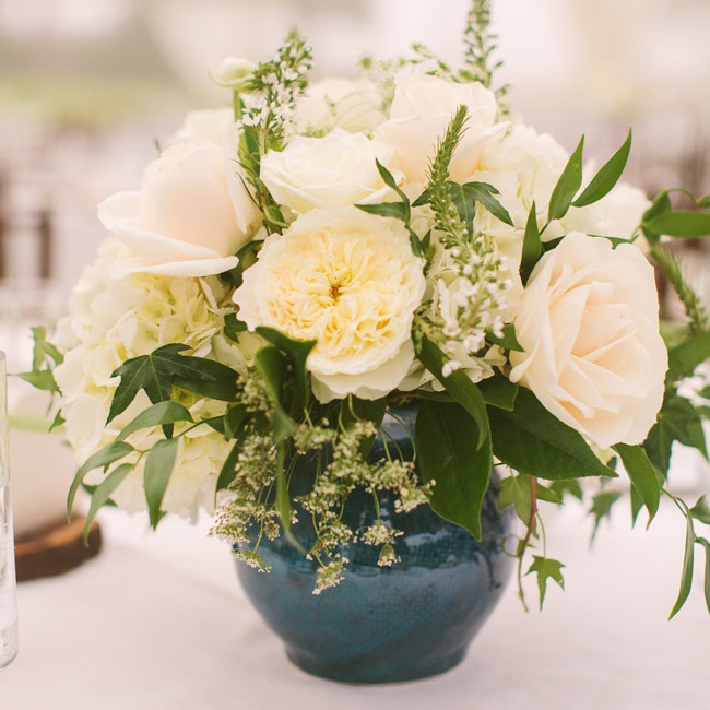 Deep blue vases topped the reception tables filled with romantic arragements of ivory blooms, including peonies, astilbe, roses and Queen Anne's lace.
