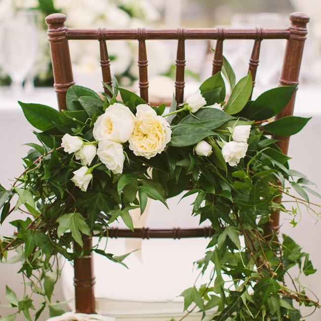 Lush green garlands with elegant ivory peonies and roses adorned the bride and groom's chairs.